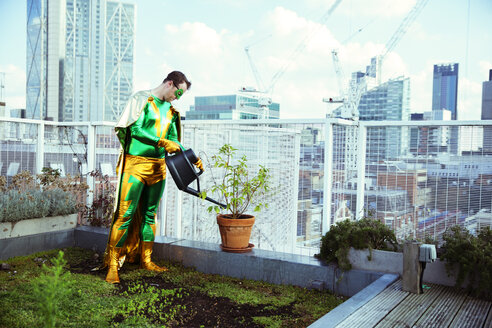 Superhero watering potted plant on city rooftop - CAIF13936