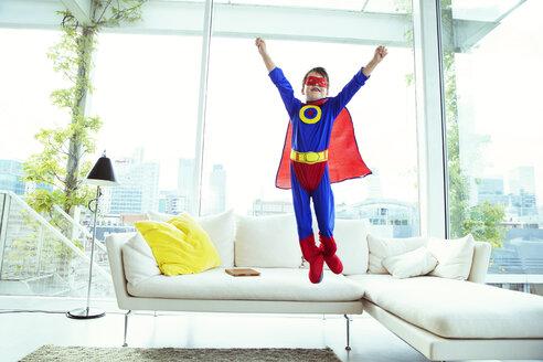 Boy superhero jumping off living room sofa - CAIF13939