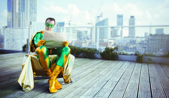 Superhero reading newspaper on city rooftop - CAIF13945