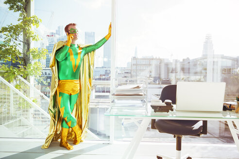 Superhero talking on cell phone in office - CAIF13948