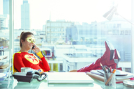 Superhero talking on cell phone at office desk - CAIF13951