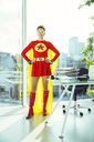 Superhero standing with hands on hips in office - CAIF13954