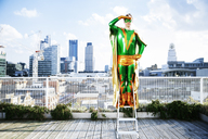 Superhero overlooking view from stepladder on city rooftop - CAIF13957