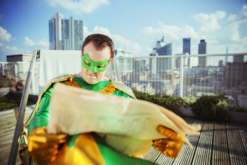 Superhero reading newspaper on city rooftop - CAIF13960