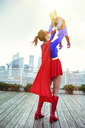 Superhero mother playing with daughter on city rooftop - CAIF13963