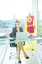 Businesswoman working at office desk with superhero costume behind her - CAIF13972