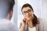 Smiling woman in glasses in office with client - CAIF13993