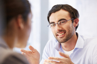 Smiling man in glasses in office with client - CAIF14005