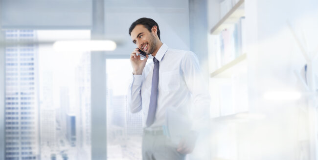 Man using smartphone in office - CAIF14008