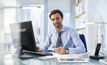Portrait of man sitting at his desk in office - CAIF14011