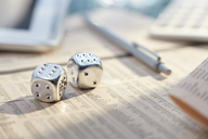Close up of silver dice with sixes on messy desk - CAIF14029