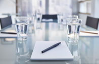 Part of modern conference room with table chairs, notepads, pens and glasses with water - CAIF14032