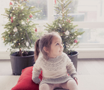 Smiling girl in front of potted trees with Christmas lights - CAIF14047
