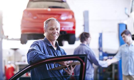 Portrait confident mechanic in auto repair shop - CAIF14068