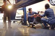 Mechanics discussing part in auto repair shop - CAIF14074