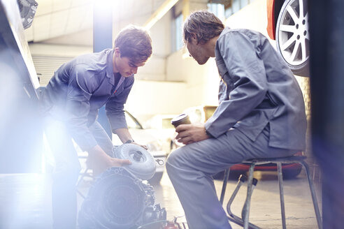 Mechanics examining engine part in auto repair shop - CAIF14077