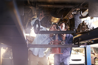 Mechanic and customer under car in auto repair shop - CAIF14083