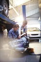 Mechanic and customer examining engine part in auto repair shop - CAIF14086