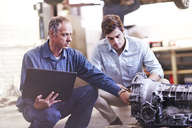 Mechanic with laptop and customer examining engine in auto repair shop - CAIF14089