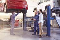 Mechanic talking to customer in auto repair shop - CAIF14092