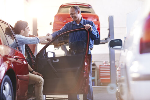 Mechanic and customer in car handshaking in auto repair shop - CAIF14098
