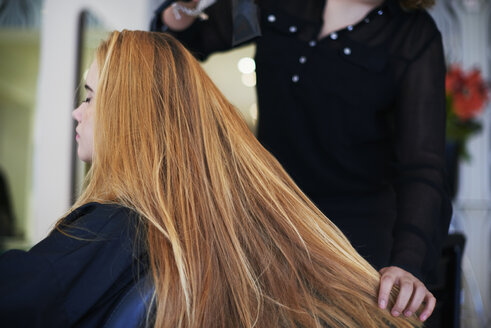 Hairdresser drying customer's long hair in salon - CAIF14101