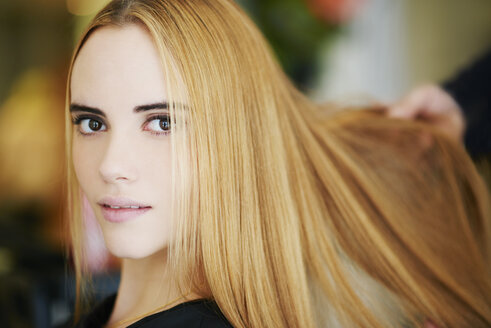 Close up portrait woman with strawberry blonde hair in salon - CAIF14104