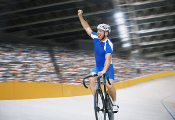 Track cyclist celebrating in velodrome - CAIF14128