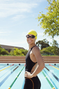 Portrait of smiling swimmer at poolside - CAIF14140