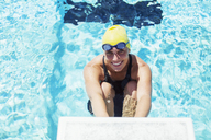Portrait of smiling swimmer poised at starting block - CAIF14164