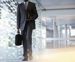 Businessman carrying briefcase in lobby - CAIF14194
