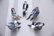 High angle portrait of smiling business people meeting in circle - CAIF14212