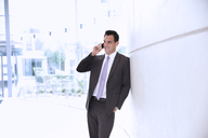 Smiling businessman talking on cell phone in lobby - CAIF14218