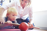 Physical therapist guiding boy rolling ball with stick - CAIF14296