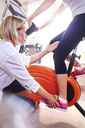 Physical therapist guiding woman's leg on stationary bike - CAIF14326