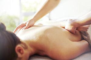Masseuse massaging woman's back - CAIF14329