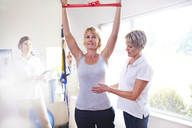Physical therapist guiding woman pulling resistance band overhead - CAIF14332