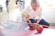 Physical therapist guiding boy rolling ball with stick - CAIF14347