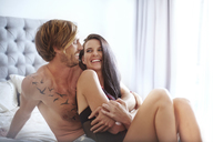 Couple laughing and hugging on bed - CAIF14398