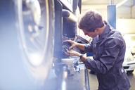 Mechanic examining part in auto repair shop - CAIF14434