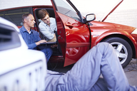 Mechanics with laptop talking at car in auto repair shop - CAIF14437