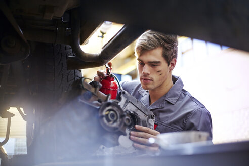 Mechanic oiling part in auto repair shop - CAIF14440