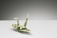 Origami crane made of dollar bill on counter - CAIF14470