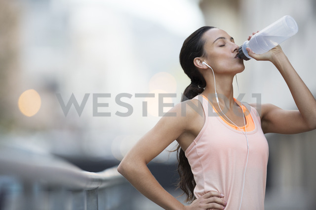 Woman drinking water after exercising on city street - CAIF14521