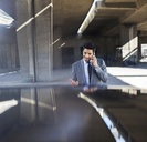 Businessman talking on cell phone in parking garage - CAIF14524