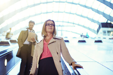 Businesswoman riding escalator - CAIF14557