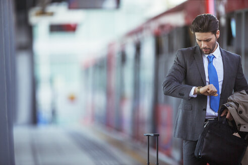 Businessman checking his watch in train station - CAIF14569