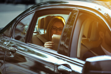 Businesswoman reading newspaper in back seat of car - CAIF14575