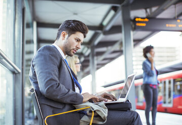 Businessman using laptop at train station - CAIF14578