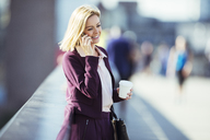 Businesswoman talking on cell phone on urban bridge - CAIF14593